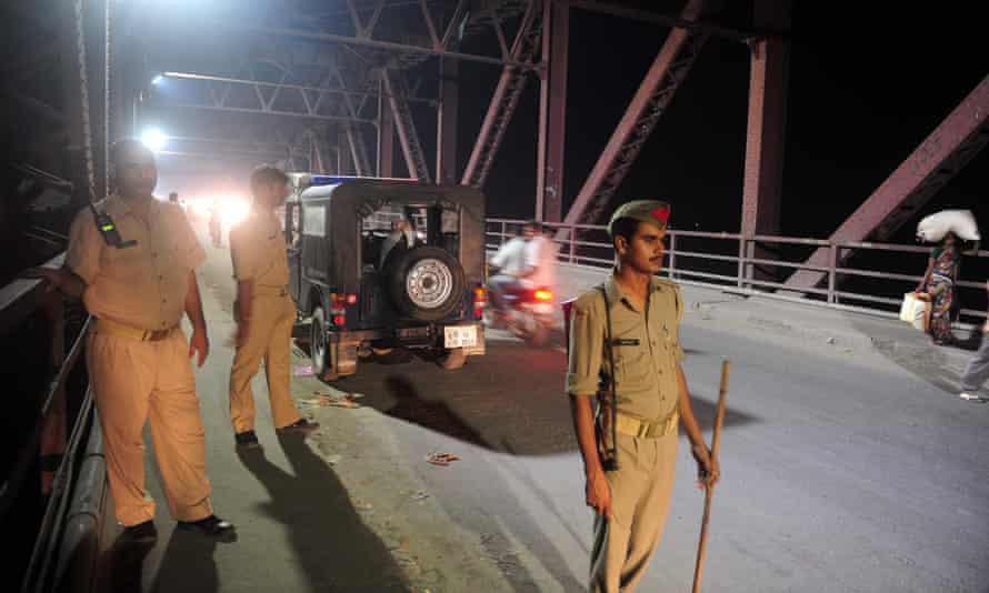 Indian policemen stand guard at the Ganga Raj ghat bridge where the fatal stampede took place in Varanasi in Uttar Pradesh state.
