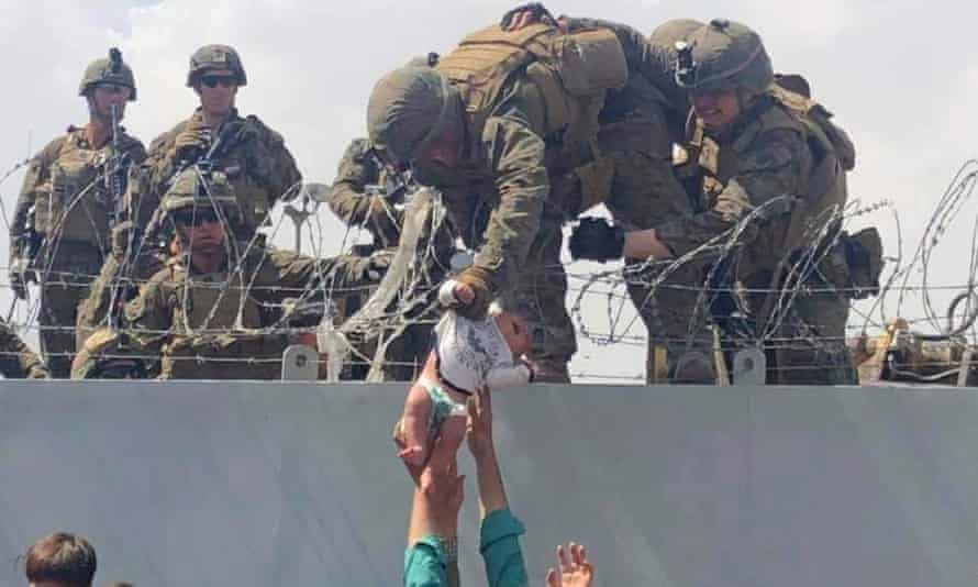 A baby is lifted across a wall at Kabul airport by US soldiers.