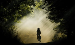 A woman on a bi bicycle ke is silhouetted against the smoke of burning hay in Laatzen, Germany