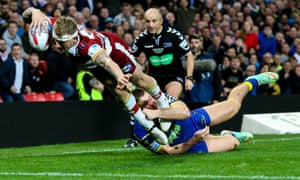 Dominic Manfredi goes over to score his second and Wigan Warriors' third try, under pressure from Warrington Wolves' Tom Lineham.