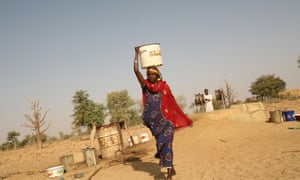 A woman carries water on her head as she returns home with water from a well in Nigeria.