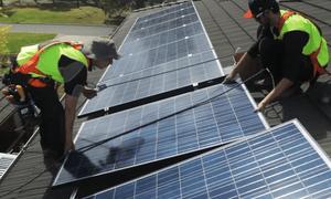 Two men in high vis vests installing solar panels on a roof