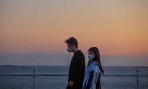 A couple walks by the sea in Long Beach, California.
