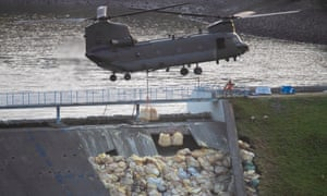 An RAF helicopter drops bags of aggregate to help shore up a broken dam wall on the reservoir above Whaley Bridge last month.