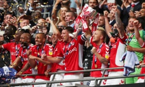 Charlton captain Jason Pearce lifts the trophy after their last-gasp win over Sunderland at Wembley.