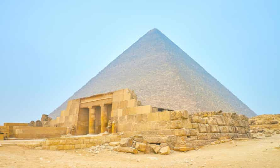 The entrance to the tomb of Queen Meresankh III, with the Pyramid of Khufu in the background, Giza, Egypt.