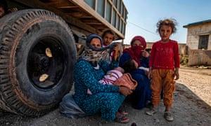 Women and children crouch under truck