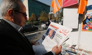 An Iranian man in Tehran holds a newspaper displaying a portrait of Donald Trump.