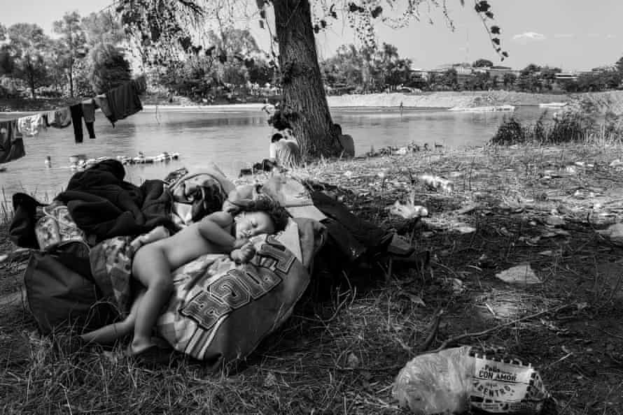 One-year-old Elan sleeps on top of a sack by the river.