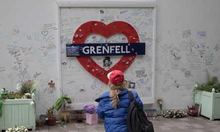 Person looking at Grenfell memorial sign, with handwritten notes on wall, and flowers on ground