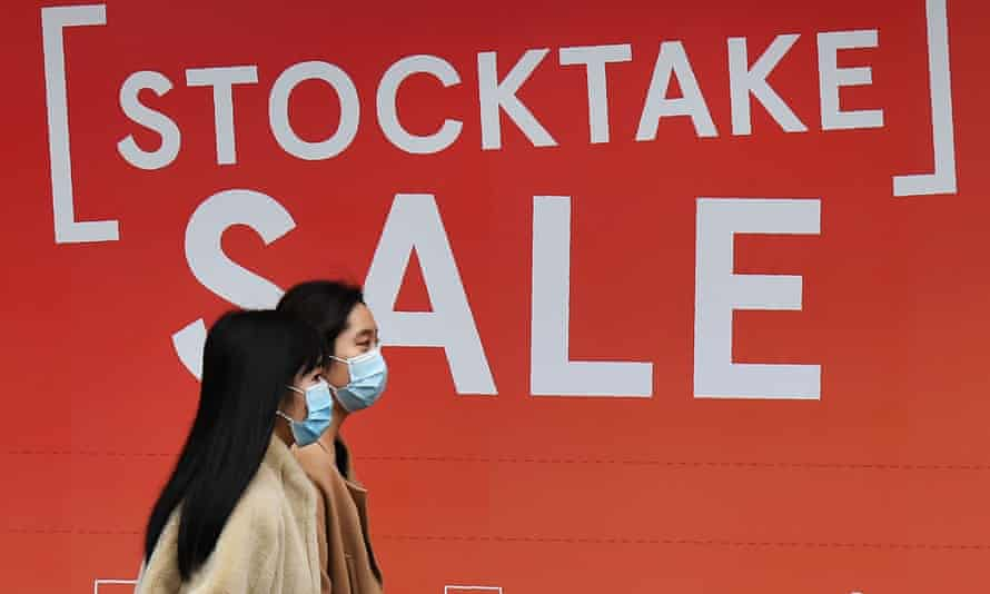 Two women walk past a sale sign in a department store window in Melbourne's CBD on Wednesday as Australia entered its first recession in nearly three decades.