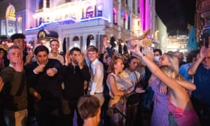 People sing and dance as they watch a street performer in Leicester Square.