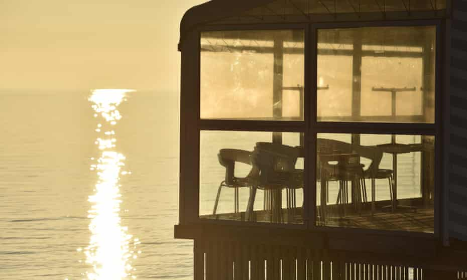 Chairs and tables stacked up in a closed restaurant overlooking the sea in Southend