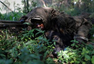 Instructor, Elliot Moseselane, lies in the bush with his dog, Alpha, both wearing camouflage snipers ghillie suits during a simulated ambush at Battle Creek K9 training facility near Rustenburg, South Africa