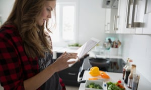 Woman with digital tablet cooking in kitchen