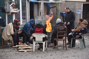 People warm themselves near a fire in a steel drum during the evacuation