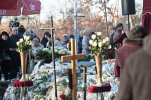 Mourners in the village of Banie gather at the grave of Polish truck driver Łukasz Urban, who was killed in the Berlin Christmas market attack