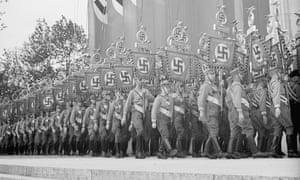 Nazi German soldiers carry banners as they march past Swastika emblems in a mass demonstration of the National Socialist Party congress in Nuremberg stadium, Germany, Sept. 6, 1938. (AP Photo)