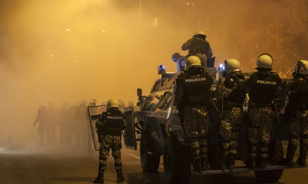 Riot police ride an armoured vehicle
