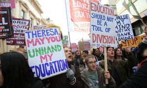 People hold placards in London on the United for Education national demonstration.