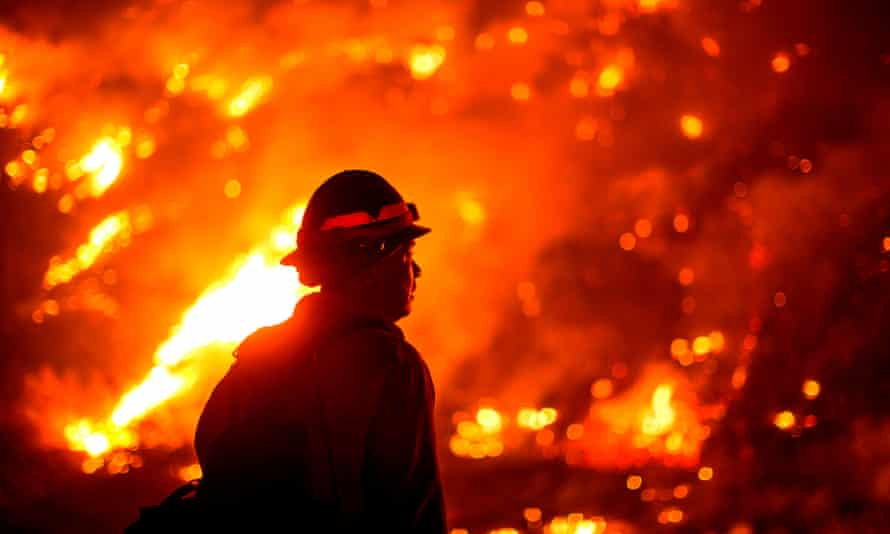 A firefighter watches the Bobcat fire burning on hillsides in Monrovia, California on 15 September 2020.