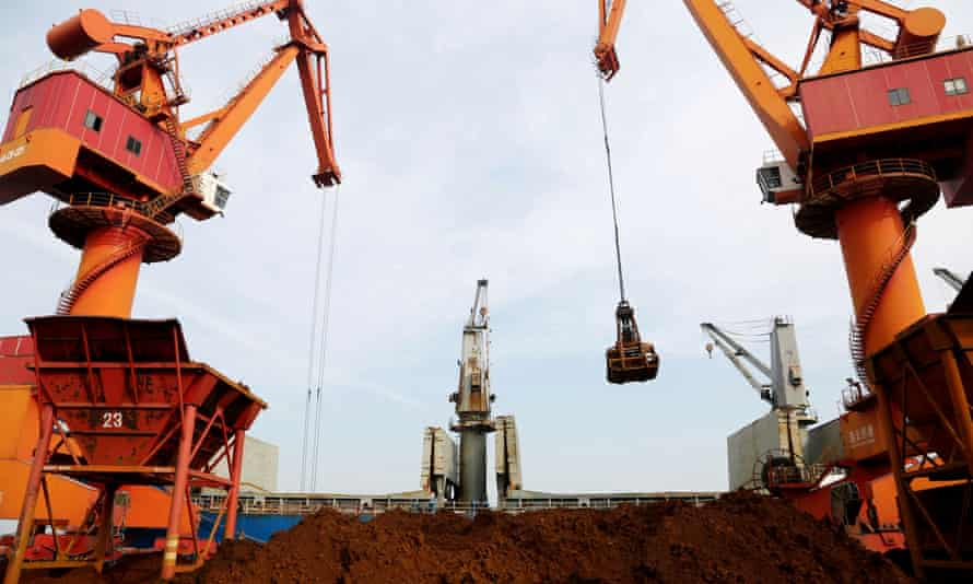 Cranes unload imported iron ore from a cargo vessel at a port in Lianyungang, Jiangsu province, China