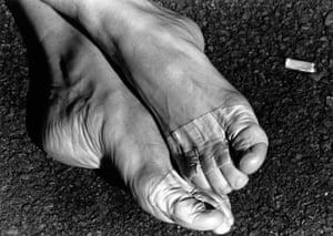 A study of a ballet dancer's feet, next to a cigarette butt.