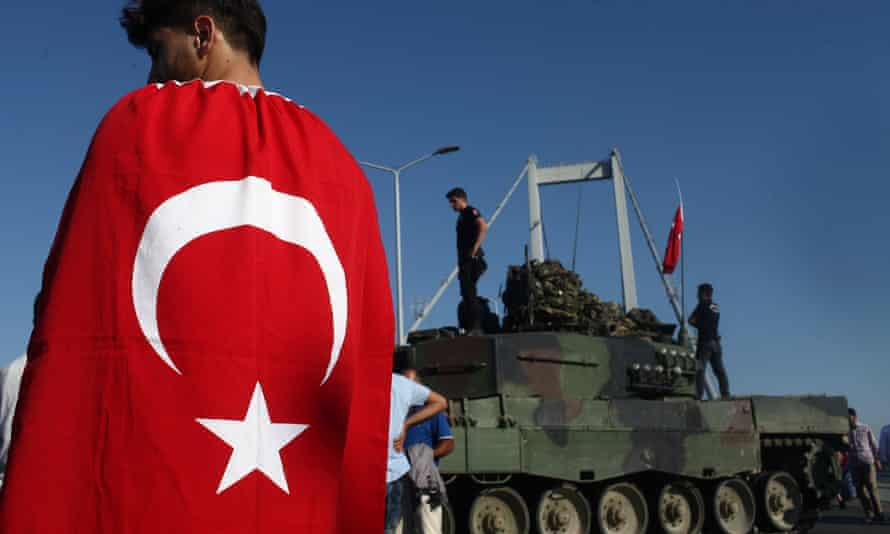 People gather around tanks abandoned by Turkish army officers on Istanbul's Bosphorus Bridge.