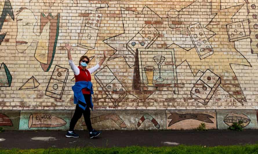 Masked woman walking past graffitied wall