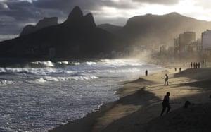 Rio De Janeiro, BrazilPeople walk at the edge of the Atlantic Ocean on Ipanema beach