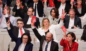 Party leader Martin Schulz (first row, centre) holds up his voting card during the SPD vote on Sunday.