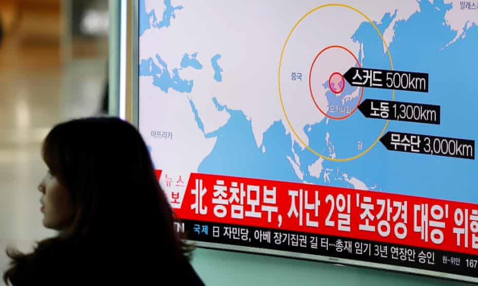 A woman in Seoul walks past a television broadcasting a news report on North Korea firing ballistic missiles.