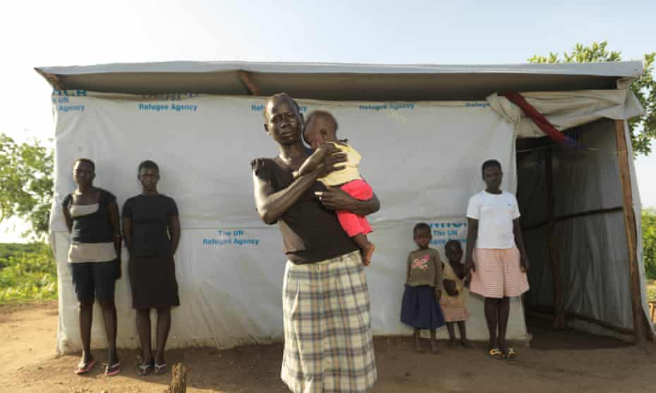 South Sudan refugee Gloria Keoji, holding her three-month-old son at Imvepi refugee settlement, flanked by her new family there, from left to right Betty Tomalu, Margaret Tomalu,  Keoji's daughter, Sharon and Zubeida Flores