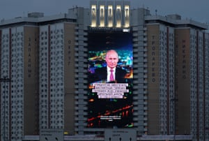 An electronic screen installed on the facade of a hotel depicts Putin during his annual address to the Federal Assembly in Moscow on Wednesday.