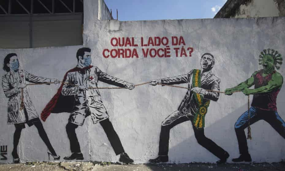 """""""Which side of the rope are you on?"""" Street art in Sao Paulo depicting health workers in a tug of war with Brazilian president Jair Bolsanaro and the coronavirus."""
