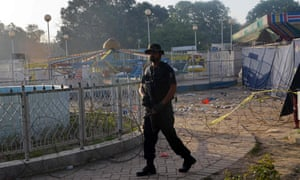 A Pakistani police commando stands guard at a Lahore following the suicide bombing that killed more than 70.