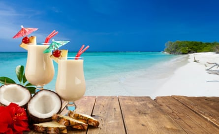 Two glasses of piña colada on wood table shot against tropical beach background
