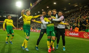 Jamal Lewis is mobbed by his Norwich teammates – and substitutes – after scoring his first Premier League goal to cut down Leicester.