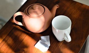 Teapot, mug and teabags sit on a wooden table
