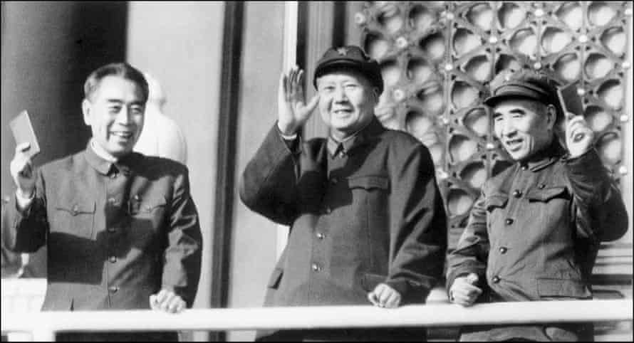 Mao Zedong with Zhou Enlai, left, and defence minister Lin Biao hold up Little Red Books as they review troops in Beijing in 1967.
