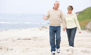 Older couple enjoying a stroll along the beach and holding hands.