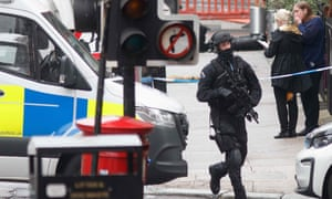 An armed specialist police officer runs as he responds at the scene of a fatal stabbing incident at the Park Inn Hotel in central Glasgow.