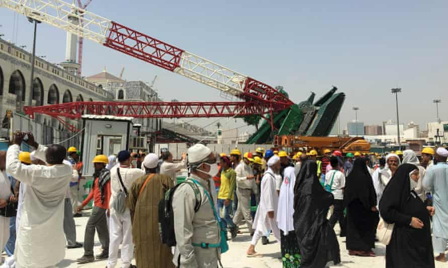 Muslim pilgrims walk near a construction crane which crashed in the Grand Mosque in the Muslim holy city of Mecca
