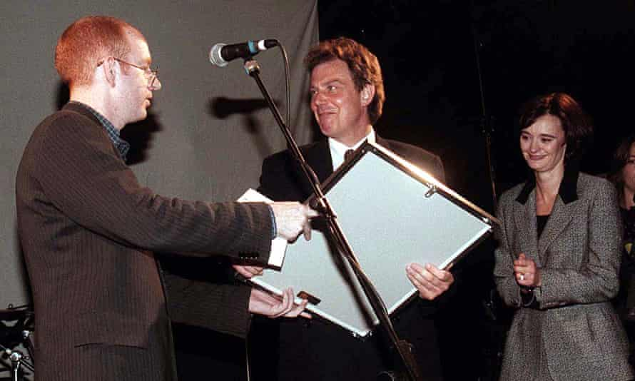 Tony Blair receiving a platinum disc of Oasis's album What's the Story, Morning Glory from Alan McGee of Creation Records in 1997