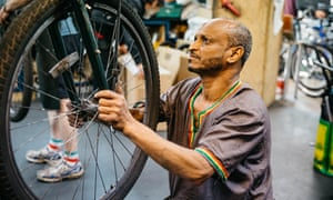 A man fixes a wheel at the Bristol Bike Project.