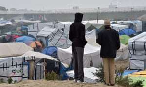 Two people look at the refugee camp in Calais.