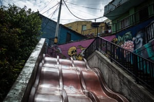 Skeletons are painted on a wall at the top of a slide in Comuna 13