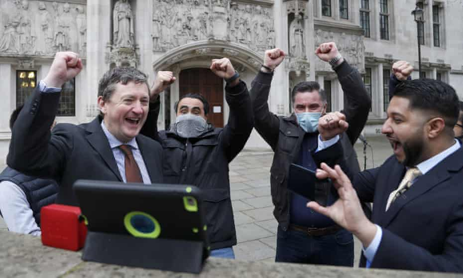 Uber drivers celebrate as they listen to the court decision on a tablet computer outside the supreme court in London
