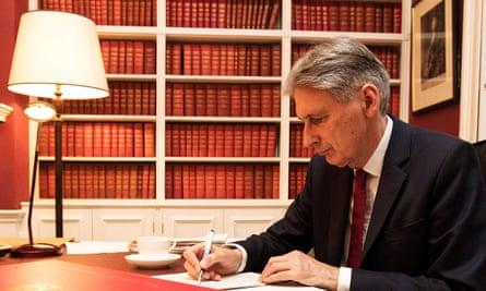 Philip Hammond writing at his desk