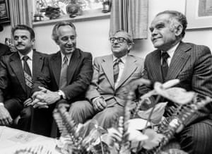 Four men including Peres sit on a sofa; all are in smart suits and ties. Peres and Navon are smiling.
